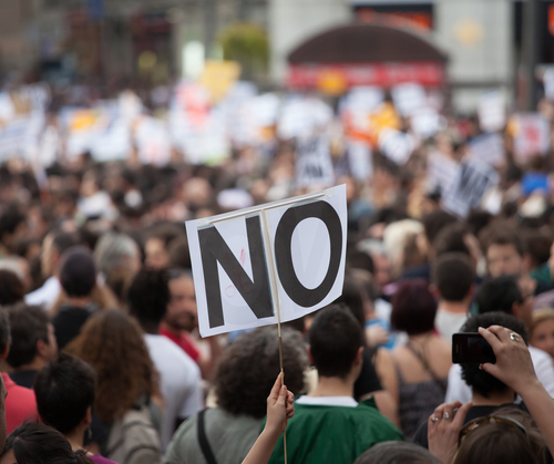 "Photo of a protestor with a ""no"" sign"