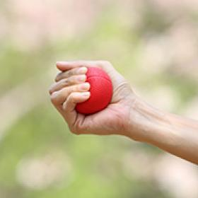 a woman's hand squeezing a stress ball